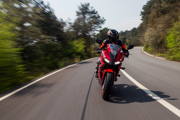 道路を走行する赤いバイク。 無料写真