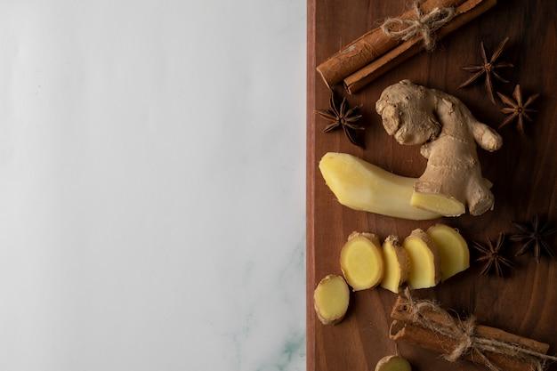 Нарезанные и очищенные растения имбиря на деревянной доске с палочками аниса и корицы Бесплатные Фотографии
