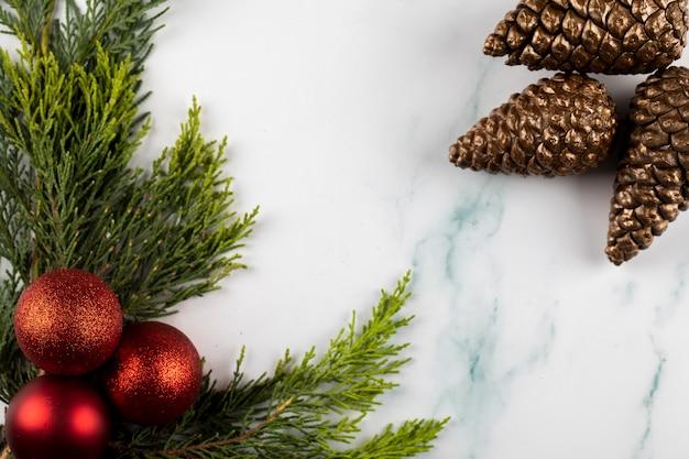 緑の枝と反対側の角にある黄金色の茶色の円錐形に赤いクリスマスツリーのボール。 無料写真