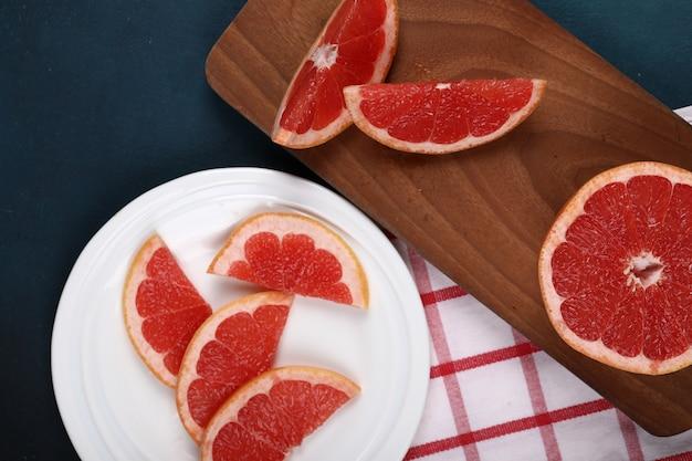 白いプレートと木の板にグレープフルーツをスライスしました。 無料写真