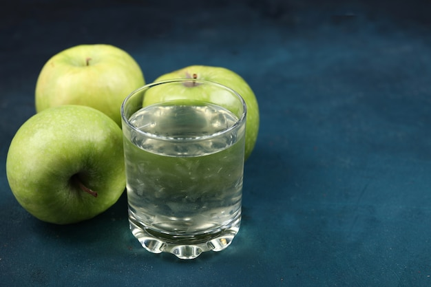 リンゴジュースのガラスと緑のリンゴ。 無料写真