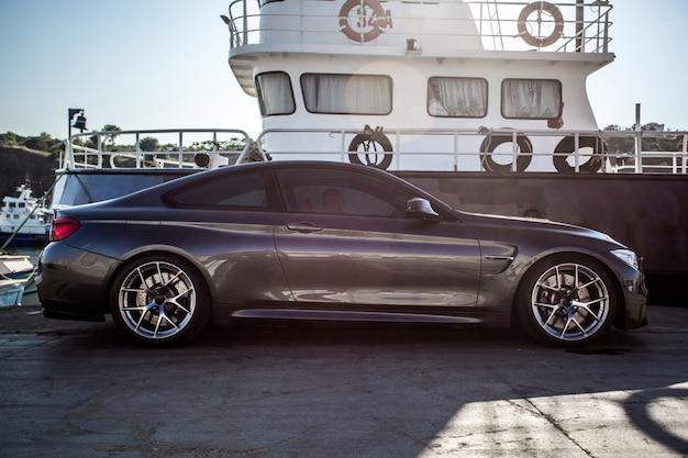 Серебряный роскошный седан припаркован в порту. Бесплатные Фотографии