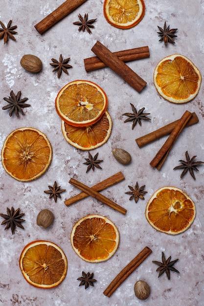 有機の自家製乾燥オレンジチップスライス、ナッツ、スターアニス、薄茶色の表面にシナモンスティック 無料写真
