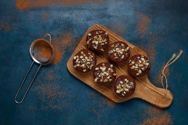 暗い表面にクルミとコーヒーカップとチョコレートクルミのマフィン 無料写真