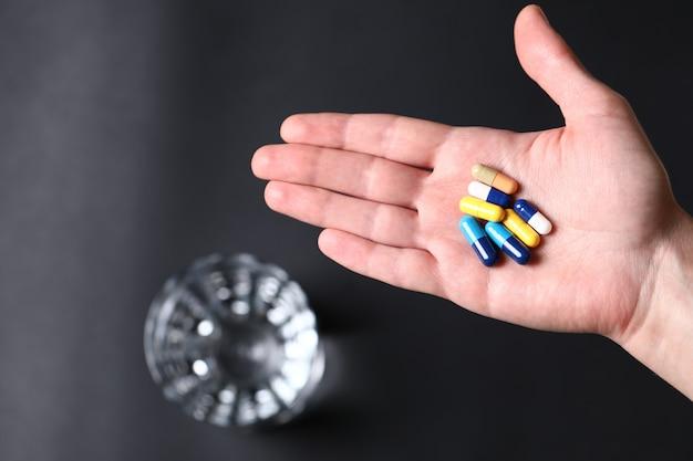 人と水のガラスの手でカラフルな医療薬 無料写真