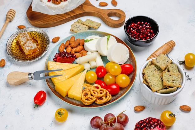 さまざまなナッツとフルーツのライトテーブルにさまざまなチーズとチーズプレート 無料写真