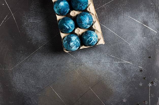 手で青い色で描かれた段ボール包装のイースターエッグ 無料写真