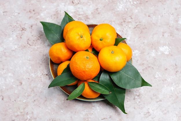 Мандарины (апельсины, клементины, цитрусовые) с зелеными листьями на бетонной поверхности с копией пространства Бесплатные Фотографии