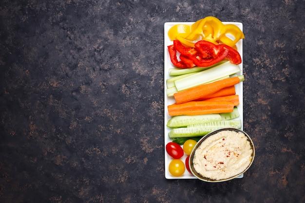 Тарелка салата из свежих органических овощей с хумусом на темно-коричневой или бетонной поверхности Бесплатные Фотографии