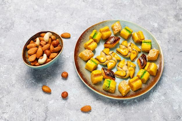 Традиционные восточные сладости с разными орехами на бетонной поверхности Бесплатные Фотографии
