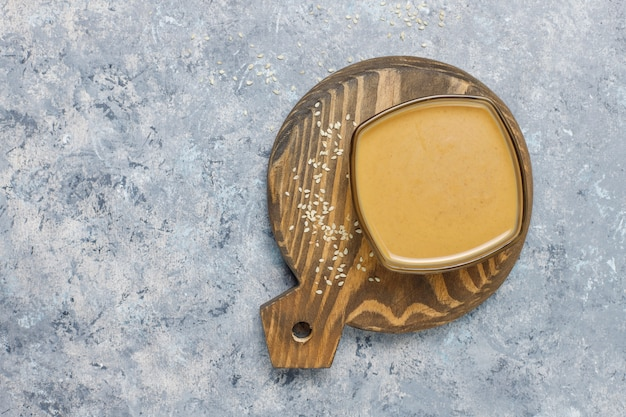 Чаша из тахини с кунжутом на бетонной поверхности Бесплатные Фотографии