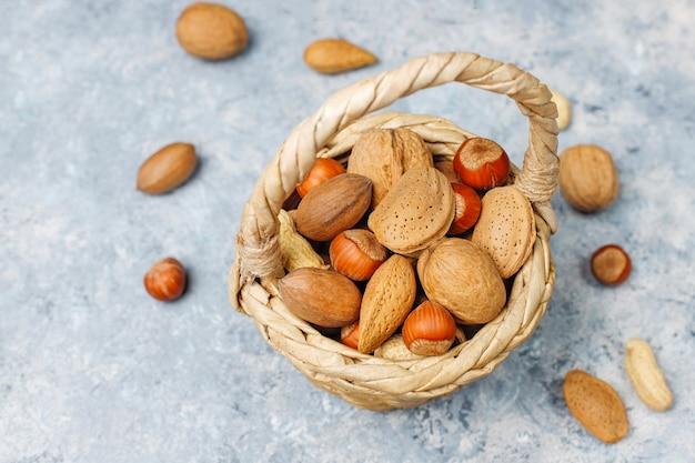 コンクリート表面のシェル、ピーナッツ、アーモンド、ヘーゼルナッツ、クルミのさまざまな種類のナッツが入ったバスケット 無料写真
