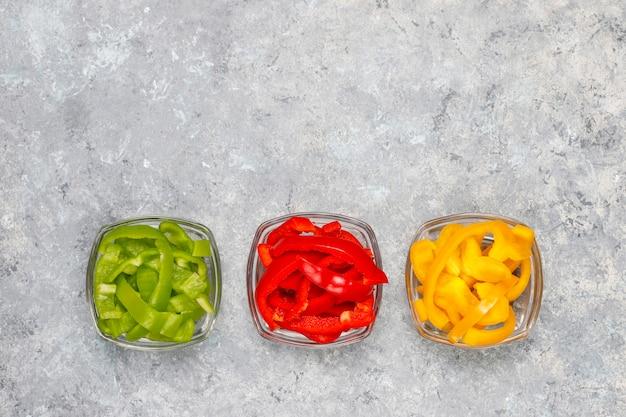 明るい面にカラフルなピーマンのスライスとまな板。異なる色のピーマンのスライス、野菜サラダ成分、健康食品の調理、トップビュー 無料写真