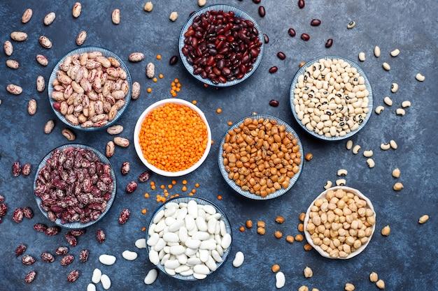 軽い石の表面の異なるボウルにマメ科植物と豆の品揃え。上面図。健康的なビーガンタンパク質食品。 無料写真