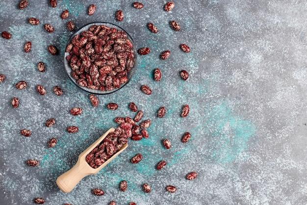 Бобовые и фасоль ассорти в разных чашах на светлой каменной поверхности. вид сверху. здоровая веганская протеиновая пища. Бесплатные Фотографии