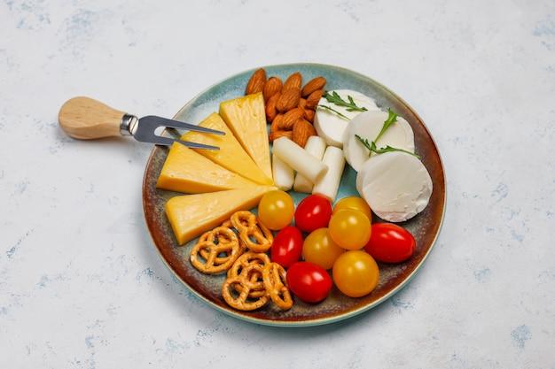 Различный сыр и сырная тарелка на светлом столе с разными орехами и фруктами Бесплатные Фотографии