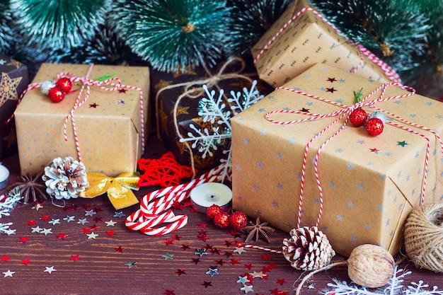 松ぼっくりモミの枝で飾られたお祝いテーブルの上のクリスマスホリデーギフトボックス 無料写真