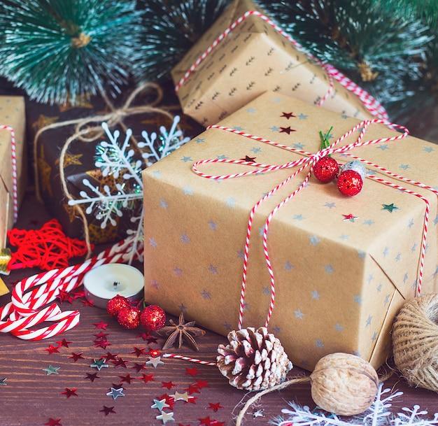 松ぼっくりモミの枝で飾られた雪のお祝いテーブルの上のクリスマスホリデーギフトボックス 無料写真