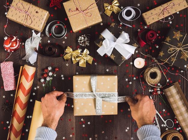 Человек, связывающий лук на рождественской подарочной коробке Бесплатные Фотографии