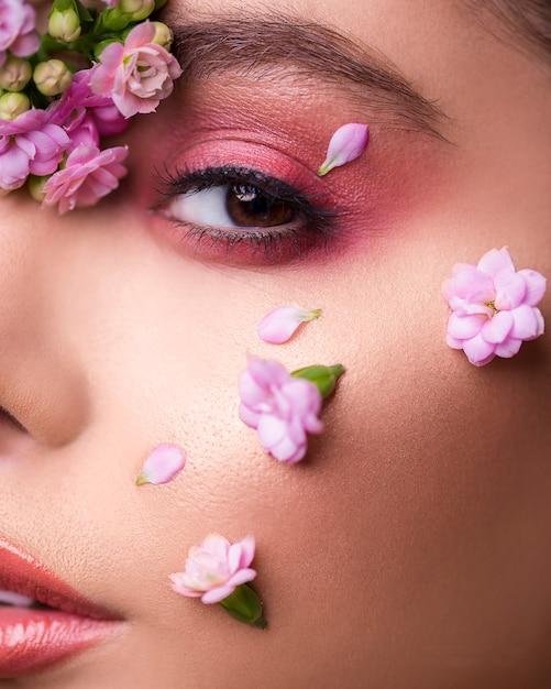 彼女の顔に花を持つ女性モデル 無料写真