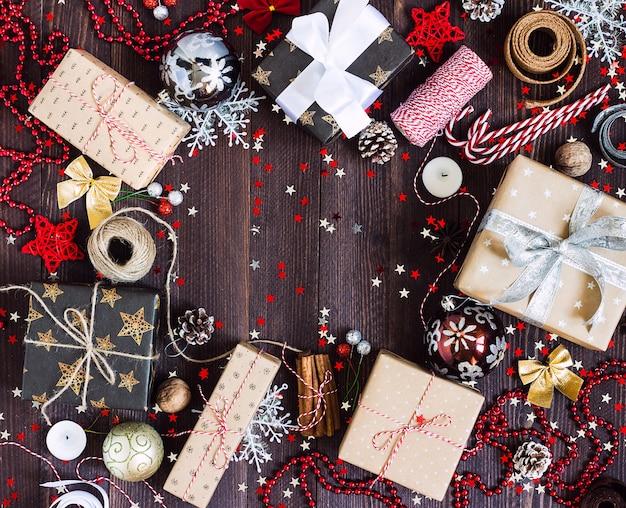 Рождественская подарочная коробка на украшенном праздничном столе с шишками из конфет Бесплатные Фотографии