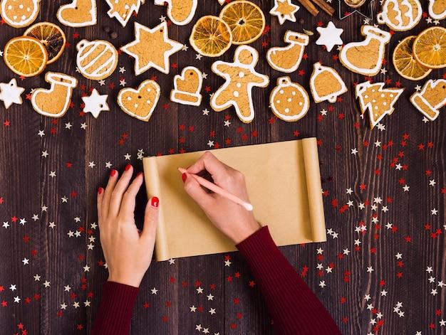 レシピクリスマスジンジャーブレッドベーキングのためのペンの空の紙を持つ女性の手 無料写真