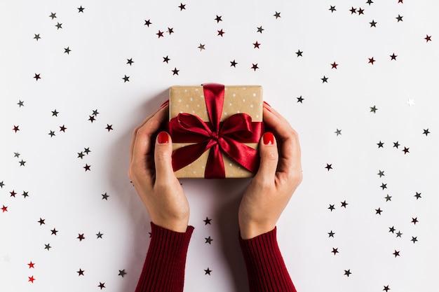 Руки женщины держа коробку подарка праздника рождества на украшенном праздничном столе Бесплатные Фотографии