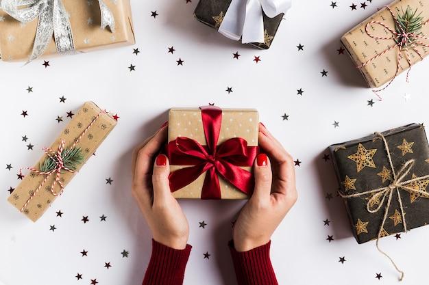 Женщина руки, держа рождественский праздник коробка подарка красный лук на украшенный праздничный стол Бесплатные Фотографии