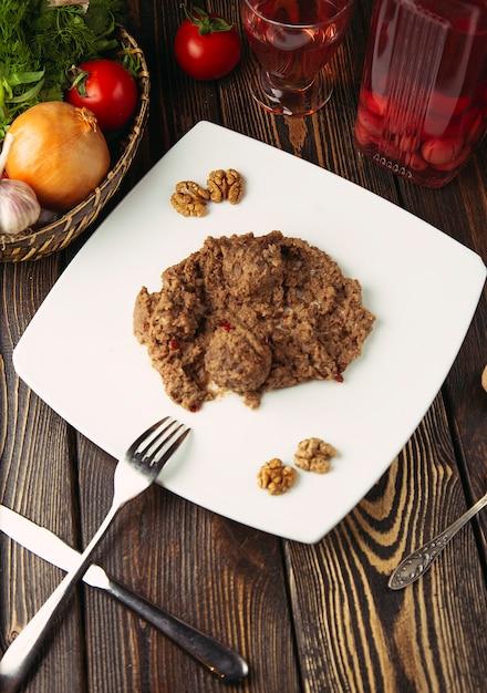Фрикадельки с соусом из ореха, подаются в белой тарелке. Бесплатные Фотографии