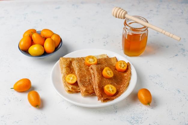 Вкусный завтрак. православный праздник масленица. блинчики с кумкватом и хонетом, вид сверху Бесплатные Фотографии