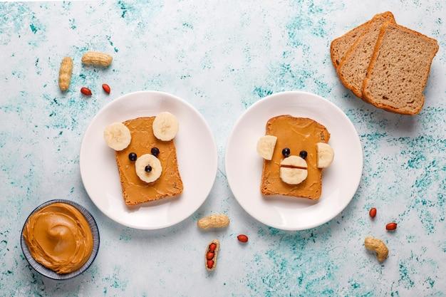 Смешной медведь и обезьяна лицо бутерброд с арахисовым маслом, бананом и черной смородиной, вид сверху Бесплатные Фотографии
