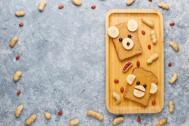 Смешной медведь и обезьяна лицо бутерброд с арахисовым маслом, бананом и черной смородиной, арахис, вид сверху Бесплатные Фотографии