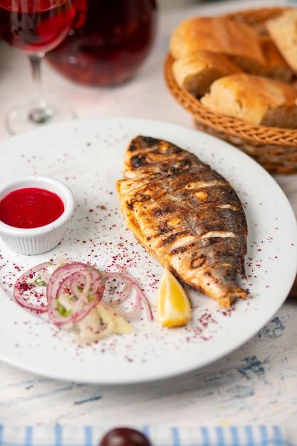 焼き魚のグリル、ハーブ、レモン、タマネギのサラダ、ディップレッドのトマトソース添え。 無料写真