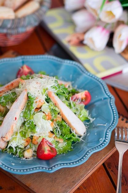 パルメザンチーズのみじん切り、新鮮なレタスとトマトのチキンシーザーサラダ 無料写真