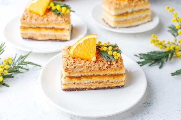 光の新鮮なオレンジスライスとミモザの花で飾られたオレンジケーキ 無料写真