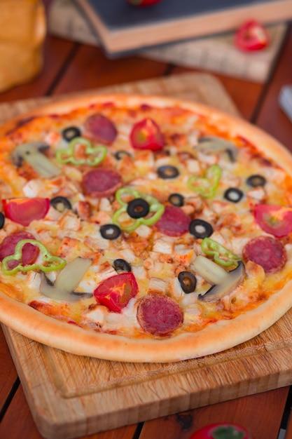 ピーマン、トマトのスライス、マッシュルーム、オリーブのペパロニピザ。 無料写真