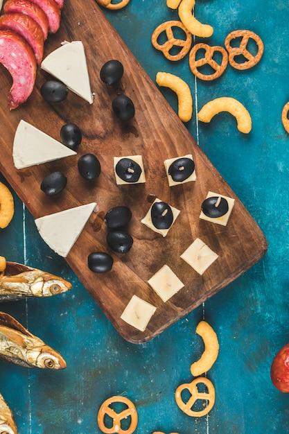 ソーセージスライスチーズキューブ、オリーブ、クラッカー、青いテーブル、上面に乾燥した魚 無料写真