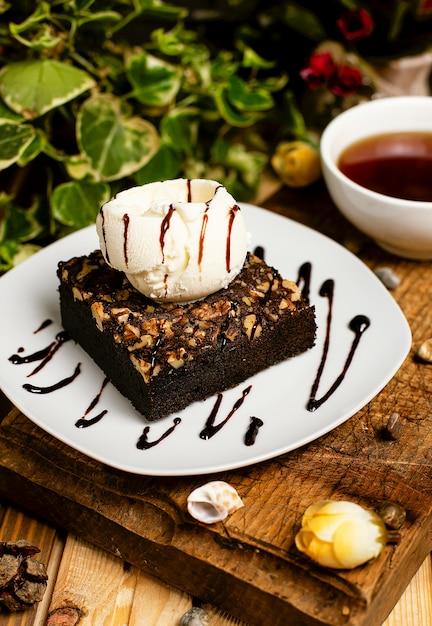 クルミとバニラアイスクリームとチョコレートのブラウニーのスライス。 無料写真