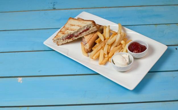 クラブサンドイッチは、ケチャップと青いテーブルにマヨネーズと白い皿にフライドポテトを添えてください。 無料写真