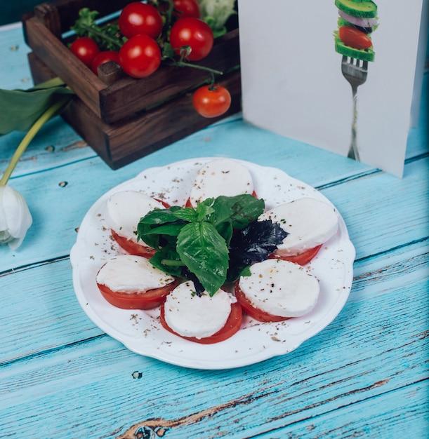 Нарезанные помидоры с сыром моцарелла и базиликом Бесплатные Фотографии