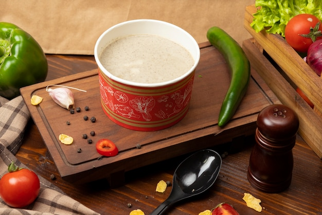 使い捨てカップボウルに入ったクリームマッシュルームスープに緑の野菜を添えて。 無料写真