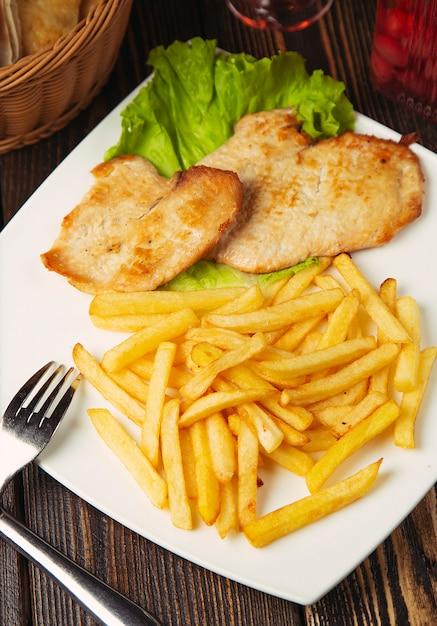 Кусочки жареной куриной грудки с картофелем фри в белой тарелке. Бесплатные Фотографии
