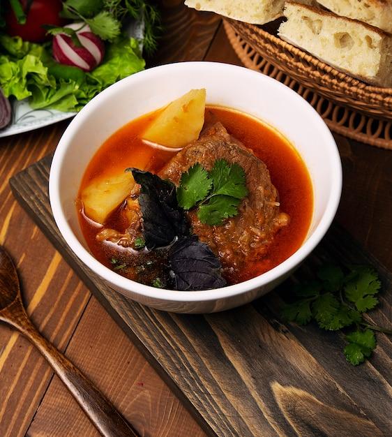 牛肉、子羊のシチュー、ジャガイモとボスバッシュのスープ、トマトソースのバジルとパセリ。 無料写真