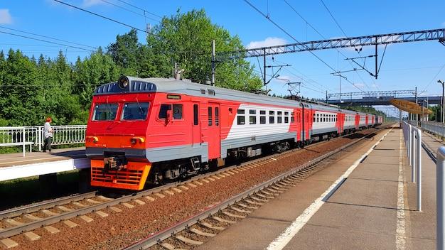 晴れた日に夏に駅に郊外の列車が到着します。途中で電車と鉄道のプラットフォーム。 Premium写真
