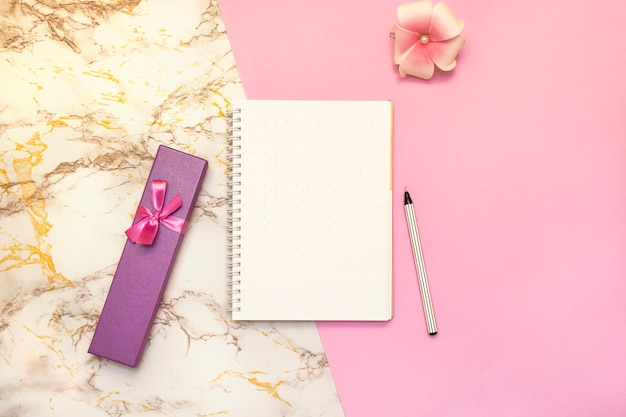 Набор женских аксессуаров письменный - блокнот с ручкой, розовая коробка подарков, цветок, вид сверху Premium Фотографии
