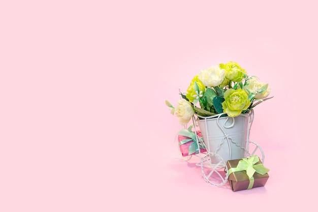 花束の花とピンクの背景のギフトボックスのポットとレトロな自転車 Premium写真