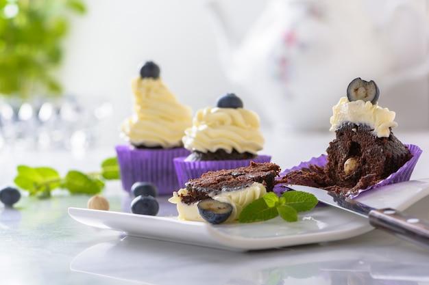 大理石のテーブルの上に紫色のラップでブルーベリーとヘーゼルナッツの白いプレートにカップケーキをカットします。 Premium写真