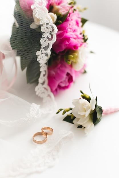 美しいピンクの牡丹の花束と結婚指輪は白いテーブルにあります。 Premium写真