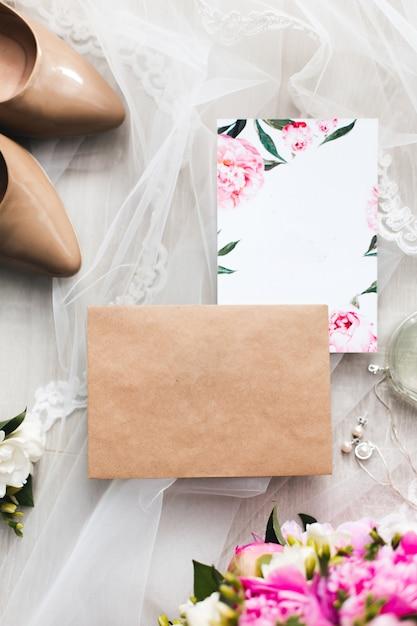 テーブルの上に置かれた結婚式の招待状のペーパーは、花、ボイル、ハイヒール、トイレの水で飾られています。 Premium写真