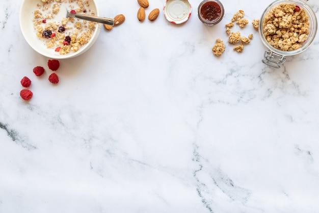 赤い果物、アーモンドミルク、大理石のジャムとクランチの朝食 Premium写真